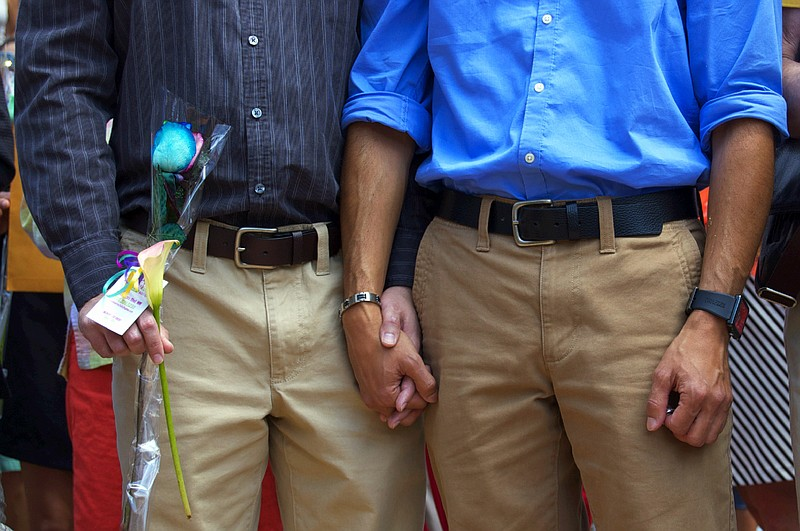Two men hold hands after getting married in Albuquerque.