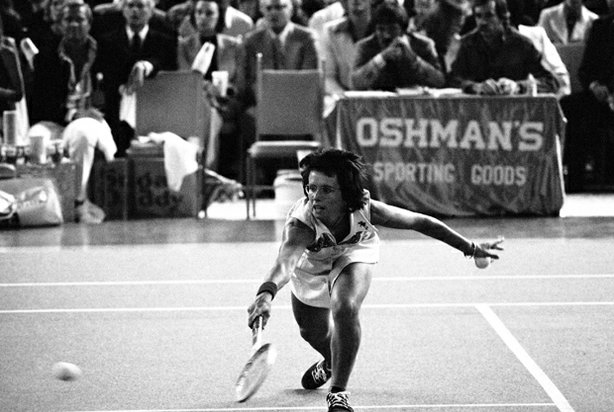 Billie Jean King bends down low to send the ball back over the net during the...