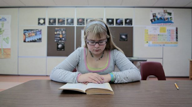 "A young girl sits at a desk reading a book as featured in ""Is School Enough?""..."
