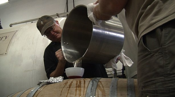 Dr. James Crute of Lightning Brewery pouring locally sourced honey to make a ...