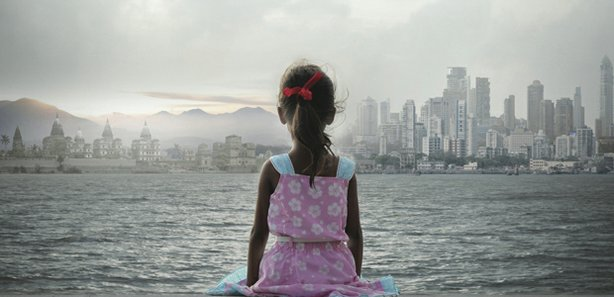 Promotional photo of a young girl sitting by the water looking at the city sk...