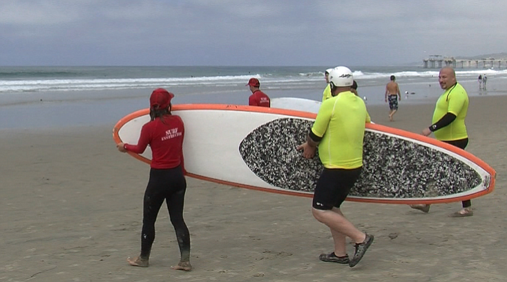 Injured veterans, wearing bright yellow shirts, head out to the waves at La J...