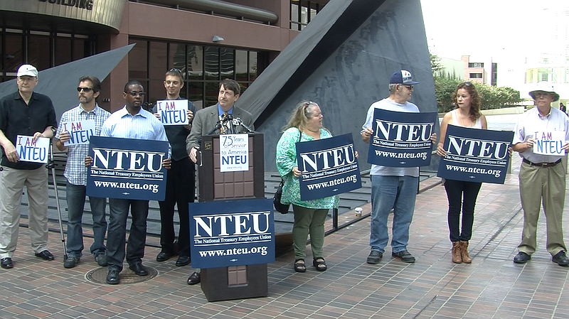 Federal employees from the National Treasury Employees Union call for an end ...