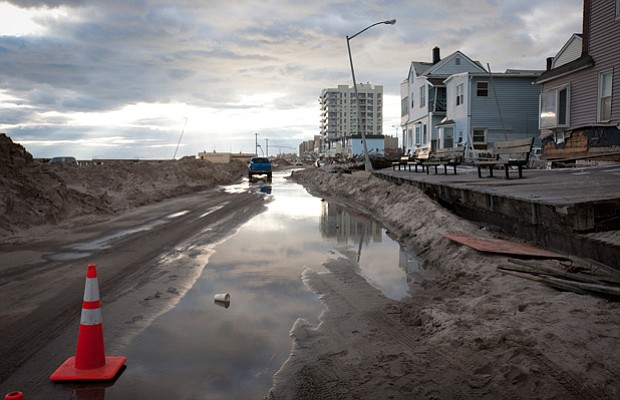 Water soaked roads filled with sand from beach in Rockaway Beach, Queens, an ...