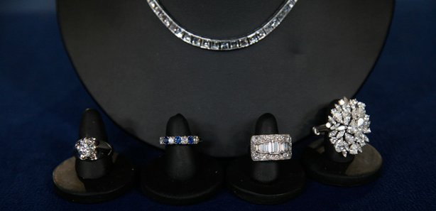 An heirloom collection of diamond jewelry dating from the late 1940s to the early 1970s, brought to the ANTIQUES ROADSHOW event in Miami Beach, Florida. From left to right: an engagement ring valued at $25,000 to $30,000, a sapphire diamond ring valued at $2,000 to $3,000, a baguette ring valued at $5,000 to $7,000 and a cluster ring valued at $8,000 to $10,000. Behind the rings sits a diamond and platinum necklace valued at $45,000 to $55,000. Altogether, appraiser Peter Shemonsky estimates the collection's worth at $80,000 to $100,000.