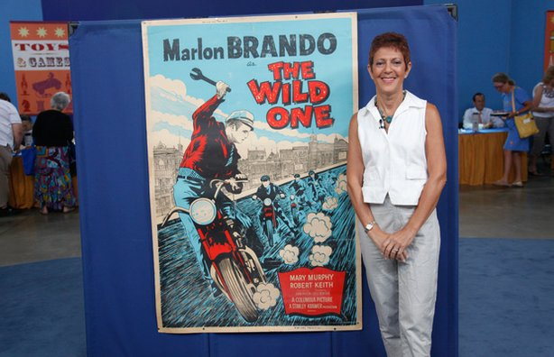 "The beaming owner of this poster, produced for the 1960 re-release of the iconic biker movie ""The Wild One,"" starring Marlon Brando. Appraiser Rudy Franchi estimates the rare, silk-screened poster to be worth $3,500 to $4,000."