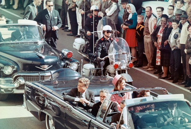 President and Mrs. John F. Kennedy smile at the crowds lining their motorcade...