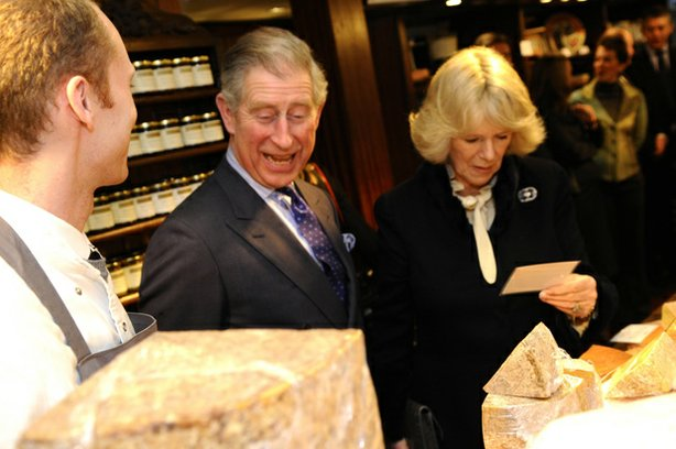 An artisan discusses cheese with Charles, Prince of Wales and The Duchess of Cornwall.