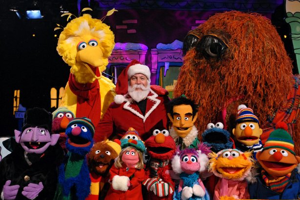 "Kevin James as Santa (center) surrounded by the cast of ""Elmo's Christmas Cou..."