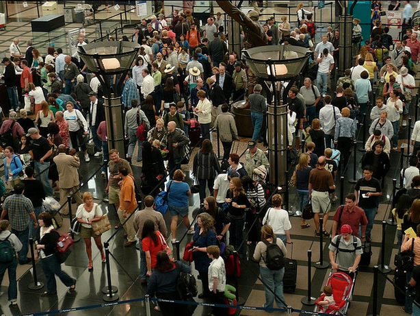 Travelers wait in an airport security line.