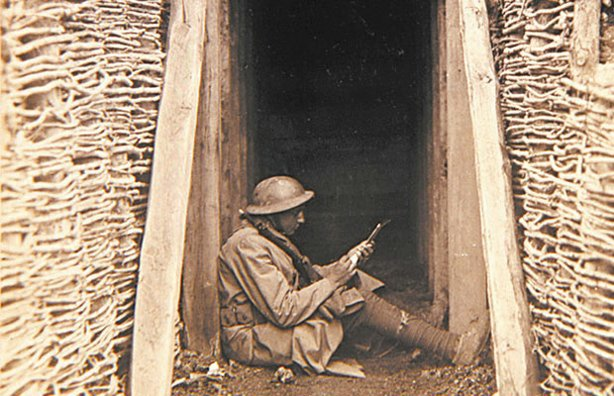 U.S. artilleryman sits on the ground writing, World War I; March 7, 1918