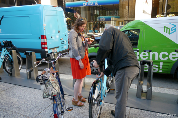 Two Chicago residents check out a bike at one of the city's bike sharing loca...