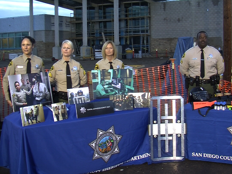 San Diego County Sheriff's employees stand behind recruitment tables during a...