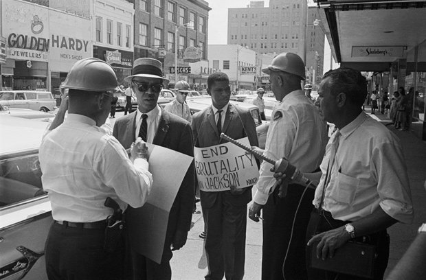 Medgar Evers surrounded by police.