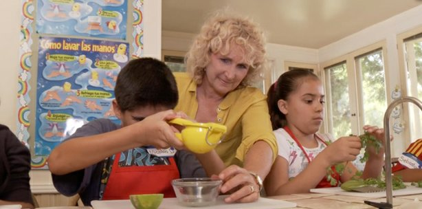 Host Nan Sterman helps students prepare a meal in the Olivewood kitchen with produce grown in Olivewood Gardens.