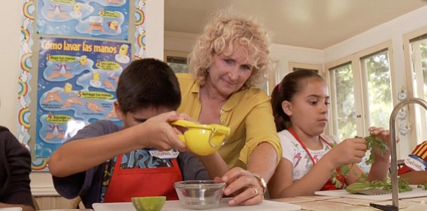 Host Nan Sterman helps students prepare a meal in the Olivewood kitchen with ...