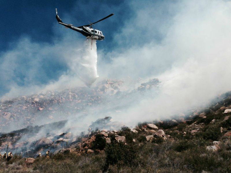 Firefighters use helicopter water drops to put out a brush fire near Alpine o...