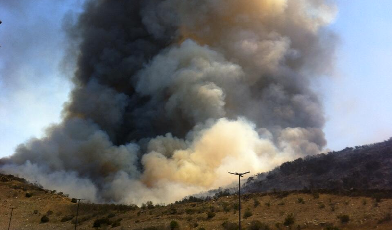 A large plume of white and black smoke rises from a hillside brush fire in Sa...