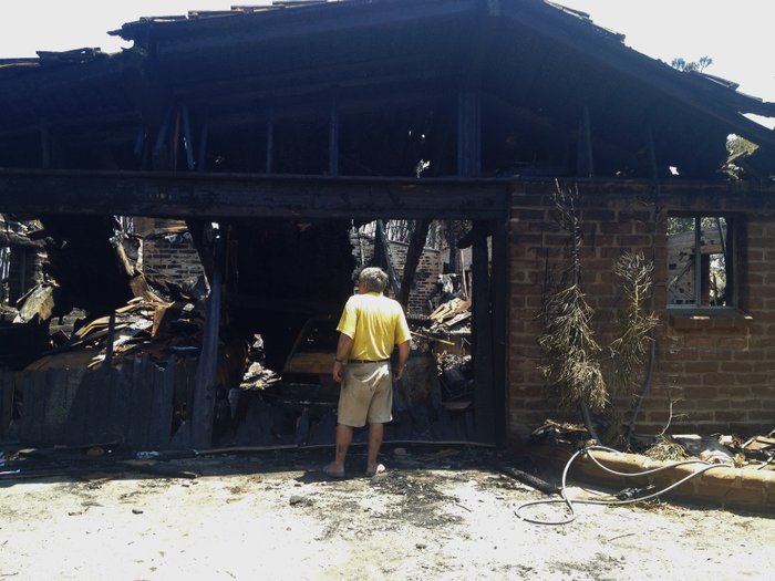 Carlsbad resident Gregory Saksa inspects the remains of his home, destroyed b...
