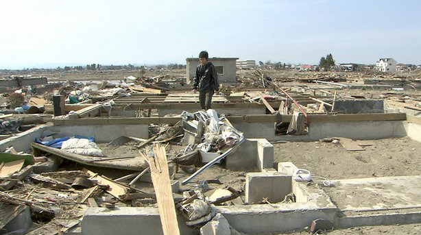 A survivor walks amid the rubble after the earthquake and tsunami that hit th...