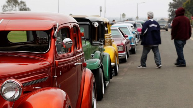 A street lined with parked customized lowrider cars.