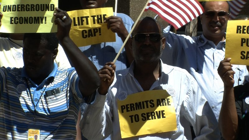 San Diego taxi drivers hold signs and wave American flags at a press conferen...