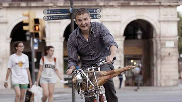 Host Phil Rosenthal bikes through streets of Barcelona with a leg of world-fa...