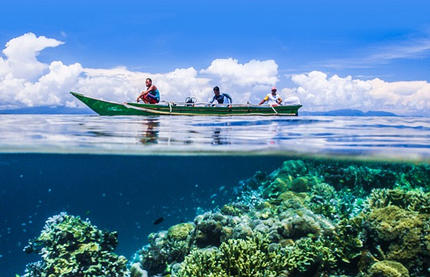 EARTH'S NATURAL WONDERS contributors on boat, Raja Ampat, Indonesia, half in ...