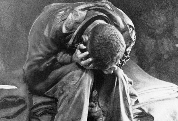 An American soldier collapses in his hands from the strain of fighting along ...