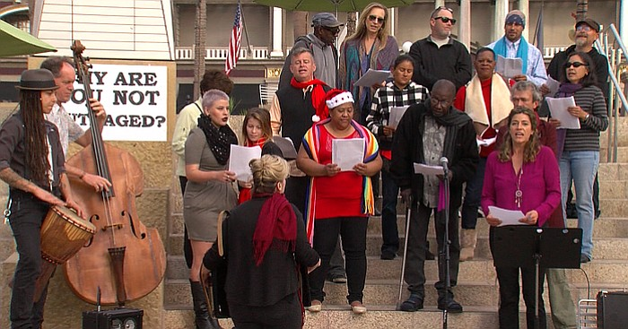 The Voices of Our City Choir sings on the steps of Horton Square to demand th...