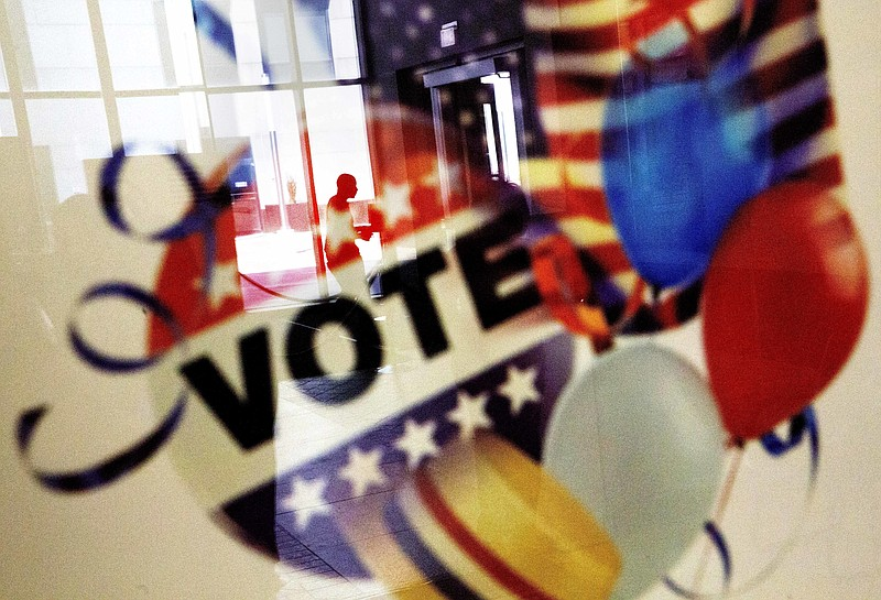 A voter is reflected in the glass frame of a poster while leaving a polling s...