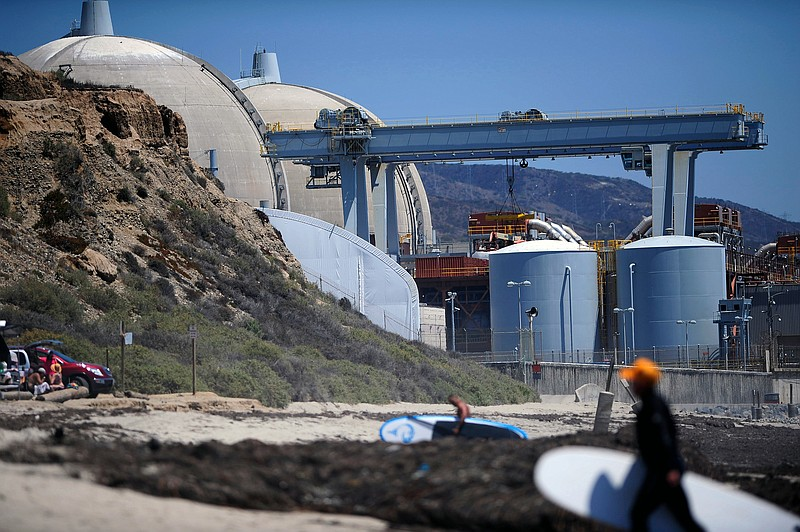 Surfers walk along a beach nearby the San Onofre nuclear power plant, July 19...