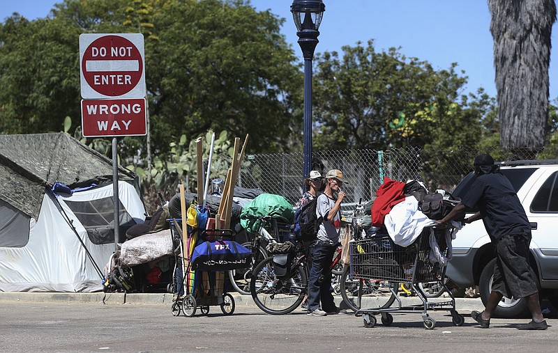 Homeless people crowd a parkway with tents and makeshift housing in San Diego...