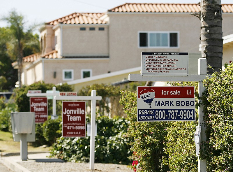 Real estate signs advertise the sale of three houses in a row in Encinitas in...