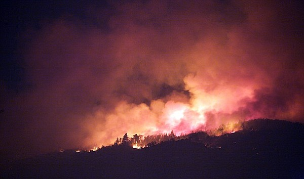 Flames from the Witch Fire light up the early Friday morning sky on Oct. 26, ...