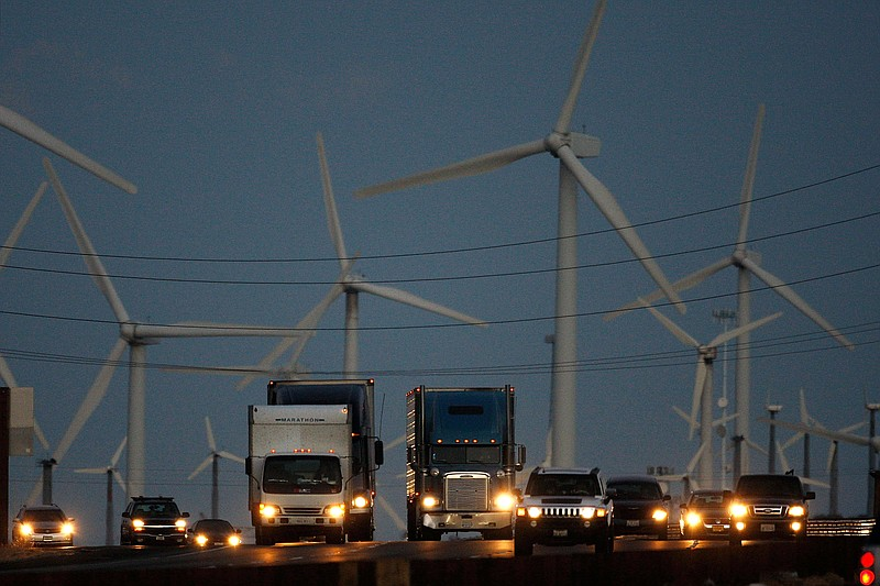 Emissions-producing diesel trucks and cars pass non-polluting windmills along...