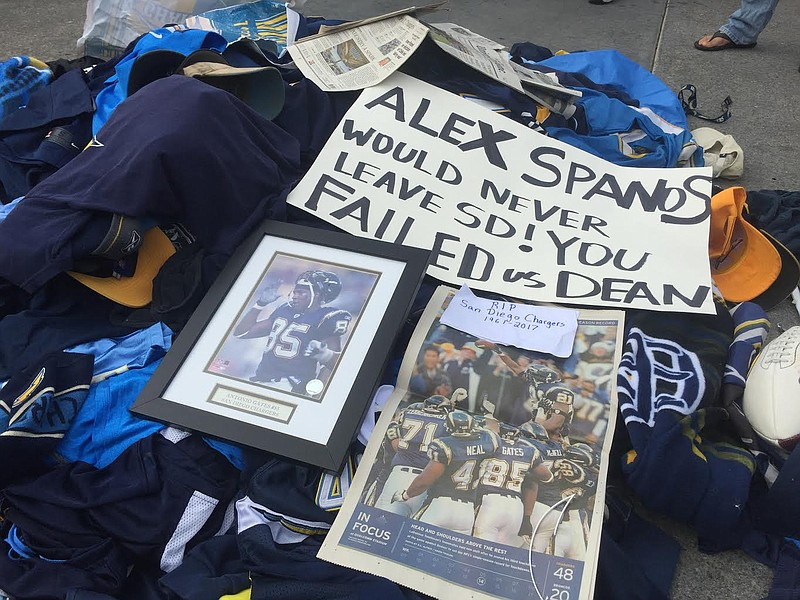 Fans toss their Chargers gear and memorabilia in front of the Chargers Team H...