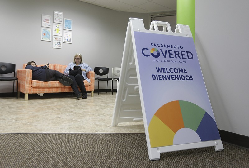 A mother and daughter wait to meet with an enrollment counselor to sign up fo...