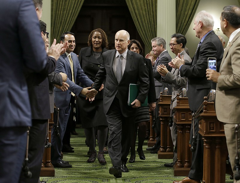 Calif., Gov. Jerry Brown is greeted by lawmakers as he enters the Assembly to...