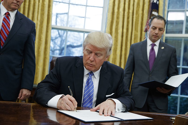 President Donald Trump signs an executive order to withdraw the U.S. from the...