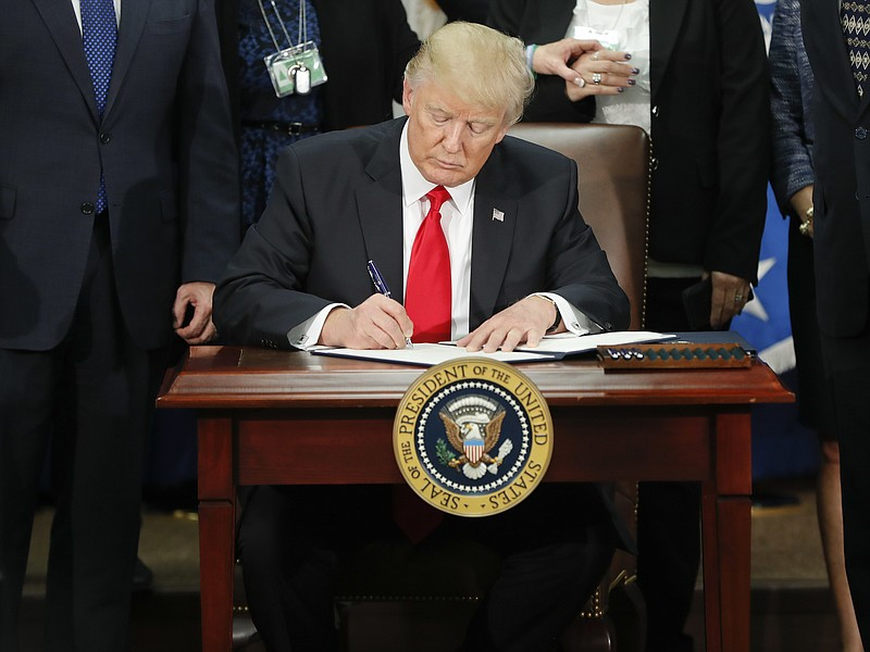 President Donald Trump signs an executive order for border security and immig...