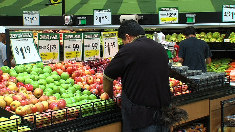 An employee checks the produce at the Food 4 Less in Market Creek Plaza on Ju...