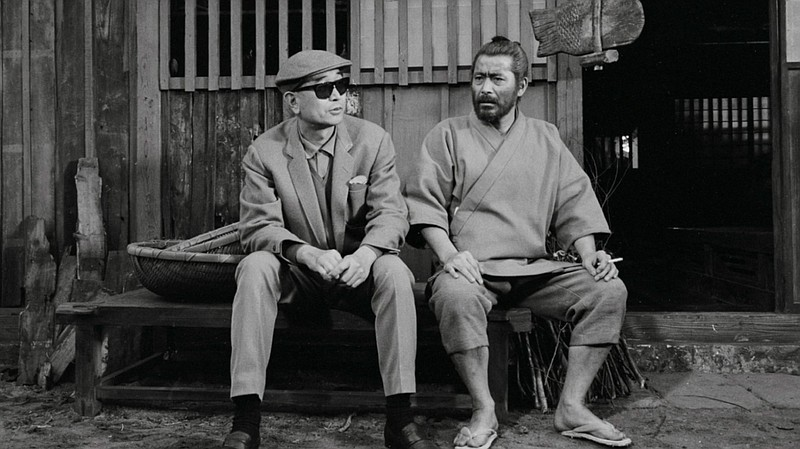Director Akira Kurosawa and actor Toshiro Mifune enjoying a quiet moment on t...