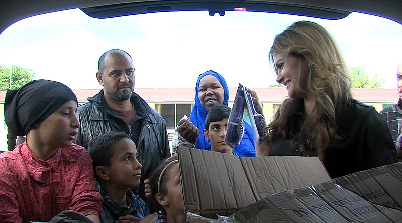 Bayanne Mihtar hands out brushes and other basic hygienic items to refugee fa...