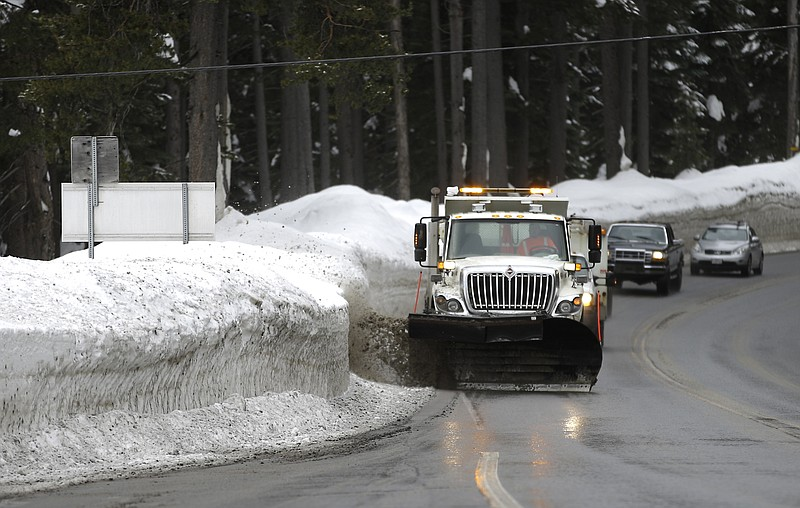 A snowplow clears snow from the side of Highway 50 near Echo Summit, Calif., ...