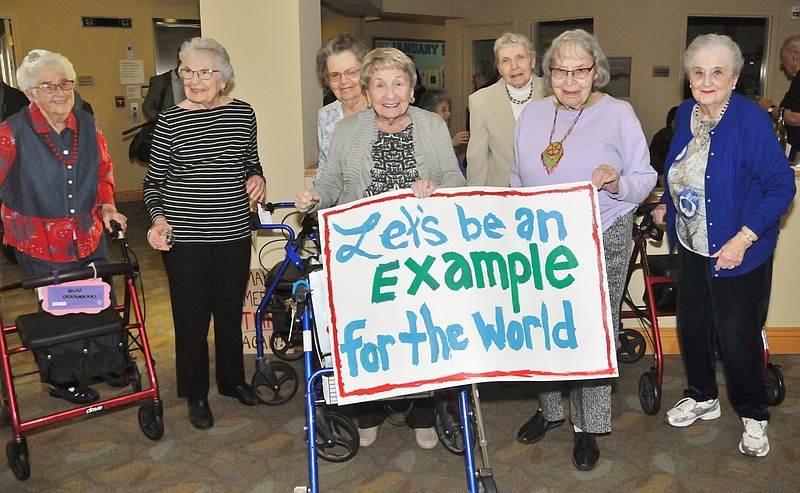 A group of women at Seacrest Village retirement home hold up a sign that read...