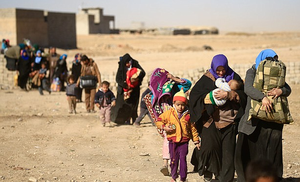 This photo shows displaced people walking in Mosul, Iraq after fleeing from I...