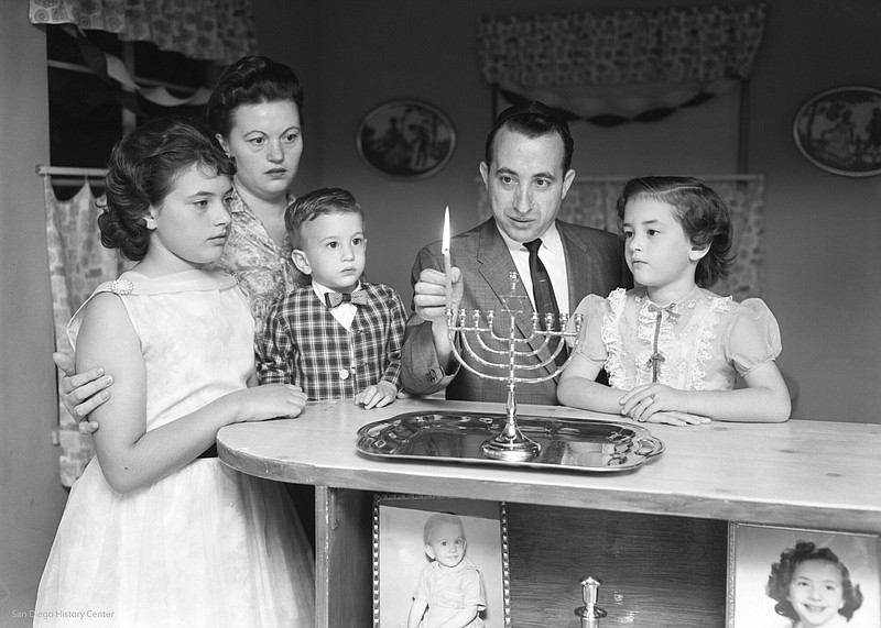 Josek Zajd lights a menorah with his family in a photograph that originally r...
