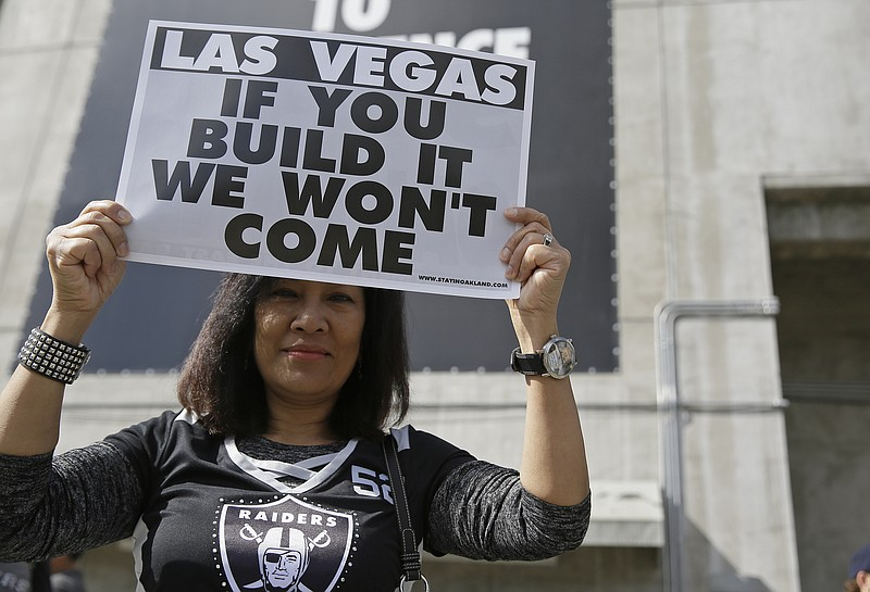 Monette Bonilla, of San Jose, Calif., holds up a sign outside the Oakland Col...