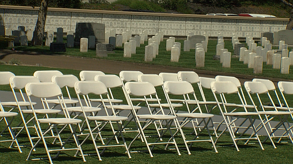 Dozens of white chairs sit empty during ceremony at Fort Rosecrans National C...